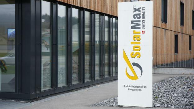 Das Bild zeigt das Gebäude der Firma Sputnik mit seiner modernen Holzfassade, davor sichtbar die Firmentafel.