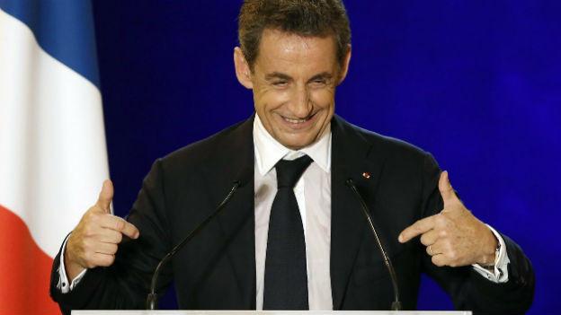 Das Bild zeigt Nicolas Sarkozy in Grossaufnahme hinter einem Rednerpodium und vor einer Frankreich Flagge. Er zeigt mit beiden Händen auf sich und lacht.