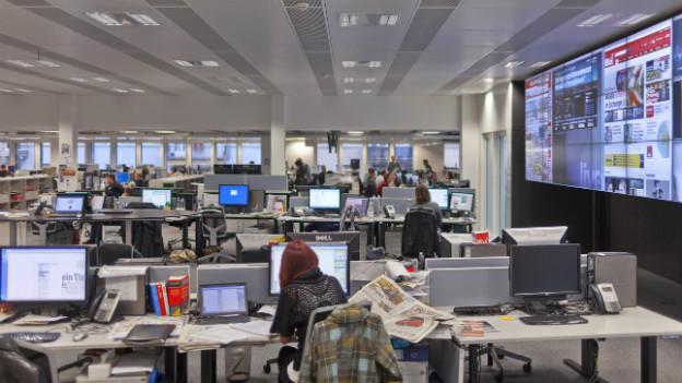 Computer, Kabel, Tische und vorne mehrere grosse Fernsehschirme. So sieht der Blick-Newsroom aus.
