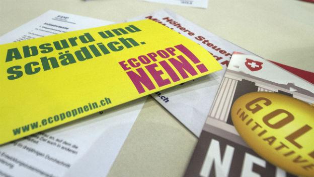 Nein-Flyer zur Ecopop- und zur Goldinitiative liegen auf einem Tisch.