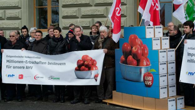 """Aktivisten von EVP, SP, Gewerkschaften und Grünen bei der Einreichung der Eidgenössischen Volksinitiative """"Millionen-Erbschaften besteuern für unsere AHV"""" im Februar 2013 vor der Bundeskanzlei in Bern."""