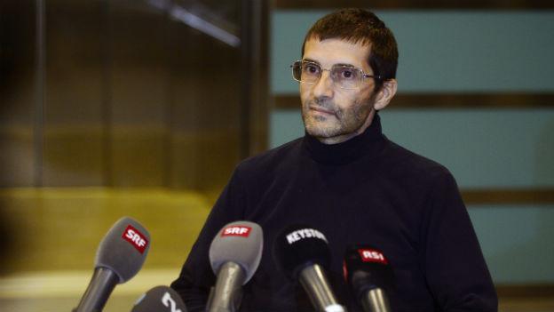 Das Bild zeigt die befreite Geisel, die an der Medienkonferenz hinter einem Tisch sitzt, vor ihm aufgestellt mehrere Mikrofone.