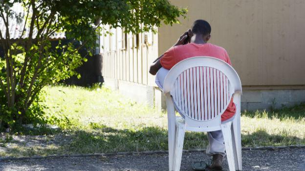 Aslyberweber sitzt auf einem Stuhl vor Asylzentrum in Zürich.