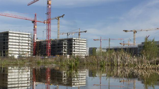 Das Bild zeigt eine Überbauung: Mehrfamilienhäuser im Bau mit Kranen, im Vordergrund ein Teich.