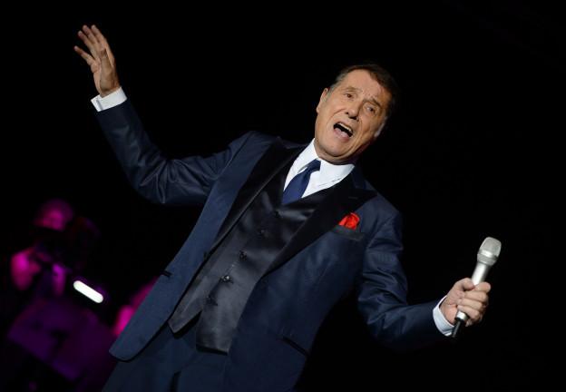 Udo Jürgens mit ausgestreckten Armen, in der Linken das Mikrofon.