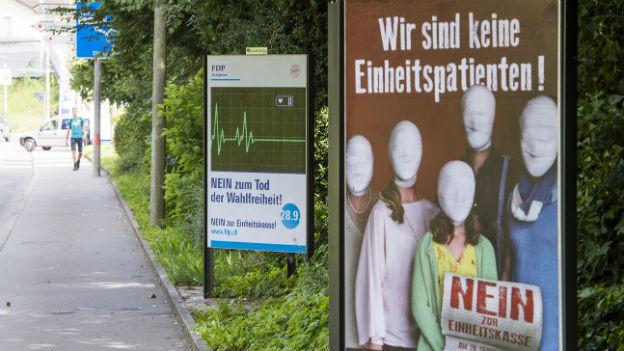 Zu sehen sind Plakate von Gegnern der Einheitskassen-Initiative