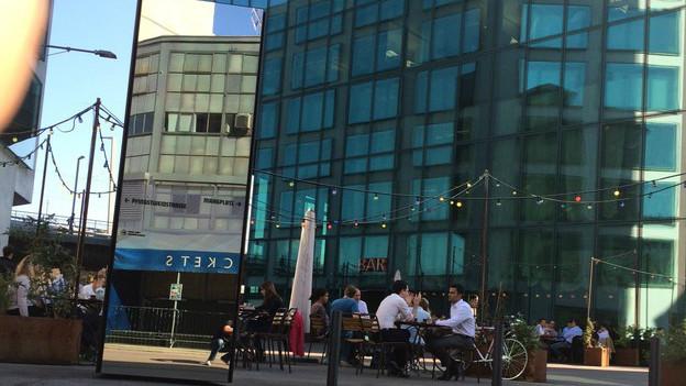 Menschen sitzen in einem Strassencafé vor dem Prime-Tower und in einem Spiegel sieht man die alte Maag-Halle.