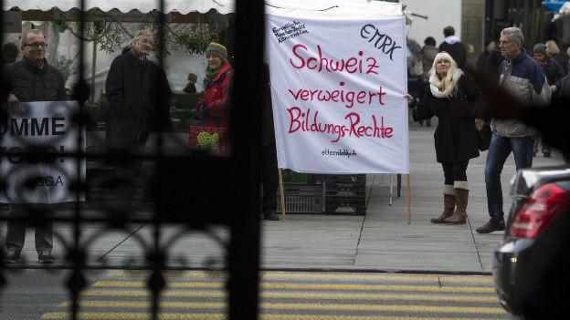 Das Bild zeigt ein Protestplakat auf dem Bundesplatz, das von einer Frau gehalten wird. Auf dem Plakat steht: EMRK; Schweiz verweigert Bildungsrechte.