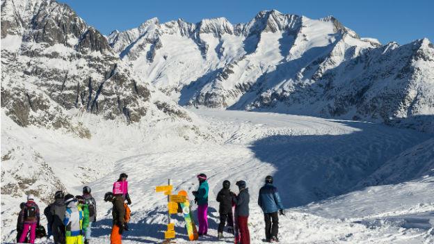 Auf dem Bild sind Wintersportler zu sehen, bei strahlendem Sonnenschein. Im Hintergrund ist der Aletschgletscher.
