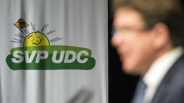 SVP-Wahlkampfleiter Albert Roesti verschwommen vor SVP-Plakat.