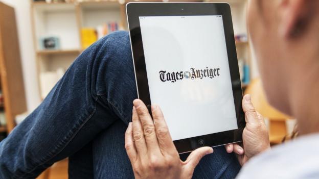 Das Bild zeigt einen Mann, Beine auf dem Tisch, iPad auf den Knien, der sich die Website des Tagesanzeigers ansieht.