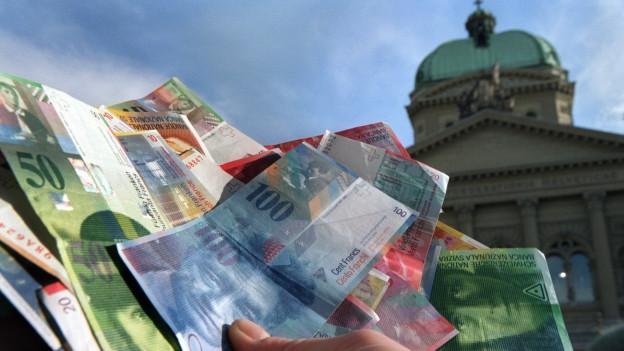 Das Bild zeigt eine Hand die Franken-Noten hält - im Hintergrund das Bundeshaus.