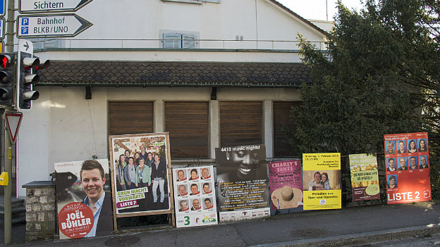 Diverse Wahlplakate sind entlang einer Strasse aufgereiht.