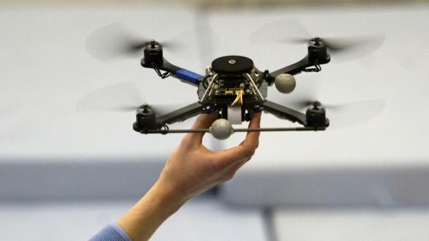 Drohne, hochgehalten von einem Mann (unsichtbar im Hintergrund).