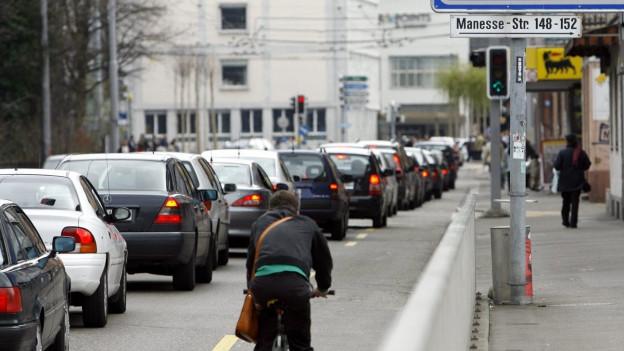 Stehende Autokolonne auf einer Strasse in Zürich (im Vordergrund Velofahrer).