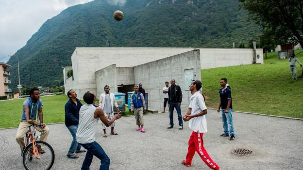 Auf dem Bild sind Menschen aus Eritrea zu sehen, die vor der Zivilschutzanlage von Lumino Fussball spielen.
