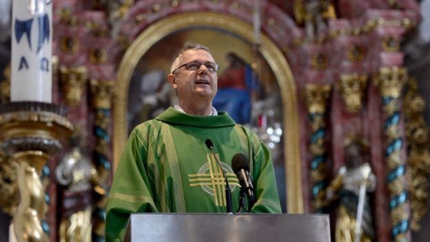 Pfarrer Wendelin Bucheli steht auf der Kanzel und Predigt, im Vordergrund eine Kerze.