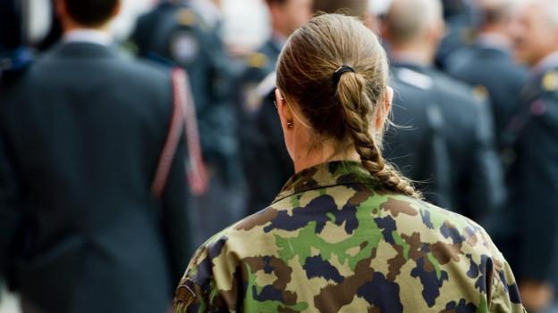 Eine Soldatin mit Zopf, die man von hinten sieht und die an einem Rapport teilnimmt.