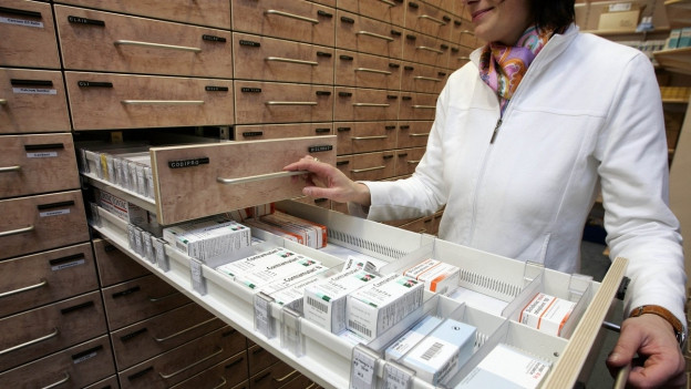 Das Bild zeigt einen modernen Apothekenschrank mit zahlreichen Schubladen. Eine Frau hat zwei Schubladen herausgezogen, sichtbar sind einige Medikamente.