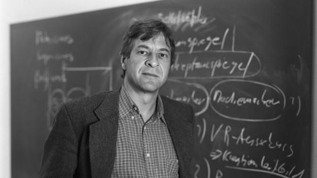 Schwarzweissaufnahme von Kurt Imhof vor einer Wandtafel, auf der mit Kreide verschiedene Begriffe notiert sind.