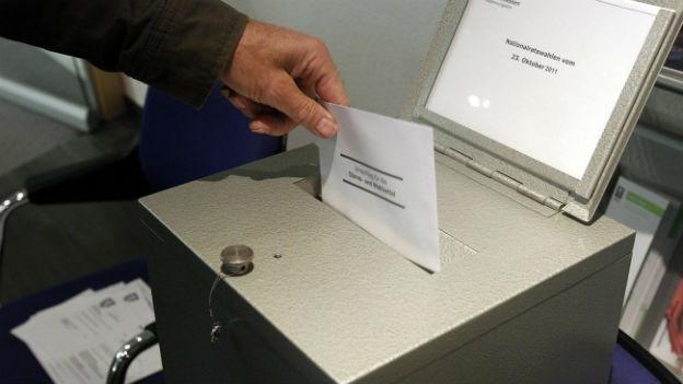 Hand wirft Abstimmungsunterlagen in Wahlurne.
