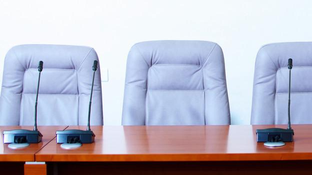 Zu sehen ist ein Symbolbild: blaue Stühle hinter einem Tisch.