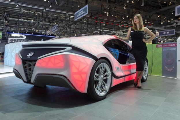 Aufnahme eines Autos am Autosalon in Genf, daneben steht eine junge Frau.