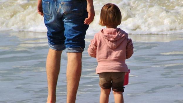 Ein Vater und Sohn stehen barfuss und mit hochgekrempelten Hosenbeinen am Strand.