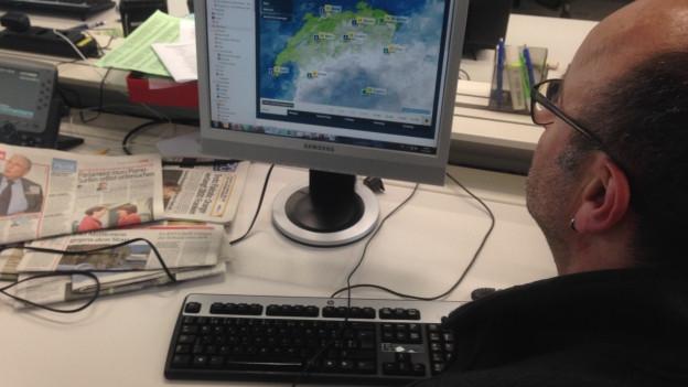 Ein Angestellter eines Unternehmens konsultiert während seiner Arbeitszeit online die Wetterprognose.