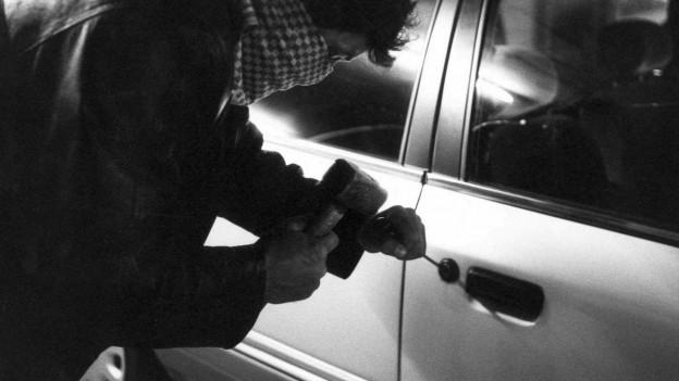 Vermummter Mann vor Auto, versucht es aufzubrechen (Bild verschwommen, gestellt).