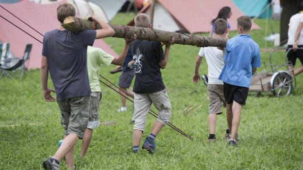 Aufnahme von drei Pfadfindern, die in einem Lager einen gefällten Baustamm auf ihren Schultern tragen.