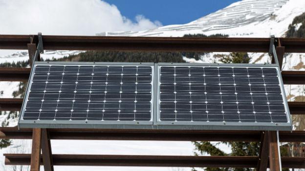 Ein Solarpanel ist an einer Lawinenverbauung befestigt.