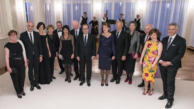Die Mitglieder des Bundesrates, teilweise mit ihren Partnern oder Partnerinnen, in der Mitte Frankreichs Präsident Hollande, im Hintergrund eine Musikgruppe.
