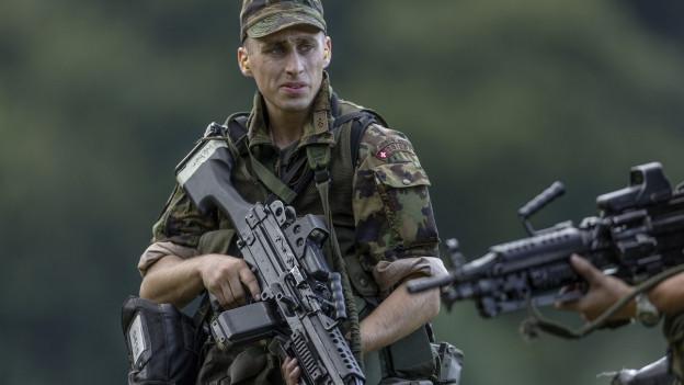 Ein Rekrut im Tarnanzug hält ein Maschinengewehr in der Hand.