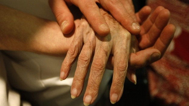 Hand eines jungen Mannes hält die Hand einer sehr alten Frau.