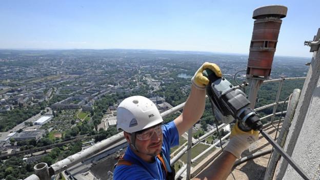 Ein Arbeiter in luftigen Höhen über der ostdeutschen Stadt Chemnitz