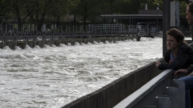 Ein Frau schaut über ein Geländer auf einen braunen Fluss.