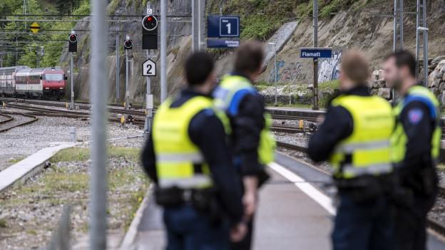 Das Bild zeigt den Bahnhof Flamatt. Im Hintergrund der gestoppte Zug, im Vordergrund 4 Männer mit Warnwesten.