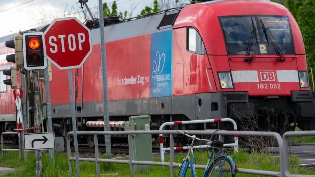 Auf dem Bild ist eine Zugkomposition der Deutschen Bahn zu sehen, die vor einem Rotlicht und einem Stop-Schild stillsteht.