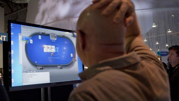 Ein Mann steht vor einem Bildschirm auf dem ein Online-Poker-Spiel zu sehen ist.