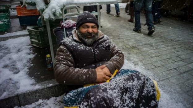 Roma-Mann sitzt im Winter auf der Strasse in Lausanne.