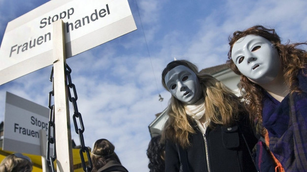 """Zwei Frauen mit einer Gesichtsmaske neben einem Plakat mit der Aufschrift """"Stopp Frauenhandel"""""""
