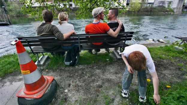 Ein hetero- und ein homosexuelles Paar sitzen auf einer Bank am Fluss, im Vordergrund spielt ein Kind.