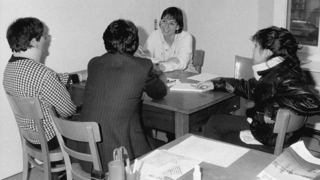 Schwarzweiss-Aufnahme aus dem damaligen Bundesamt für Flüchtlinge BFF (1987), das Dolmetscher bei der täglichen Arbeit zeigt.