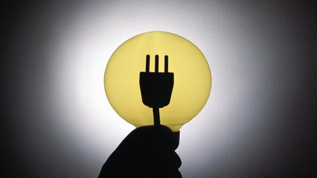 Aufnahme eines Steckers, der gegen eine gelbe Glühbirne gehalten wird.