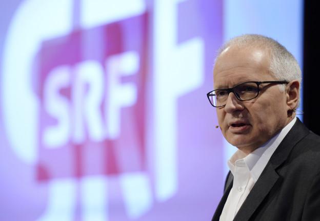 Das BIld zeigt Ruedi Matter, SRF-Direktor, vor dem SRF-Logo