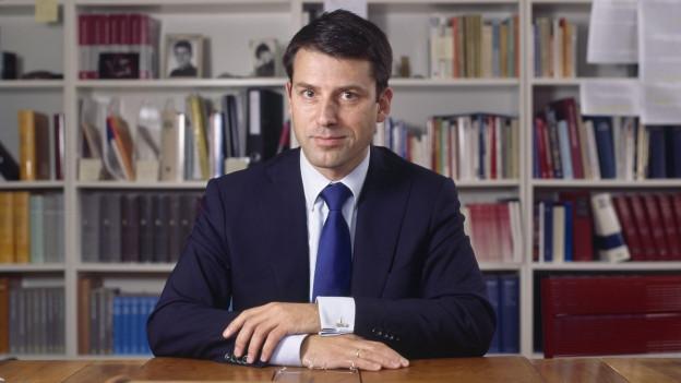 Gottfried Locher sitzt in einem Büro vor einer Bücherwand.