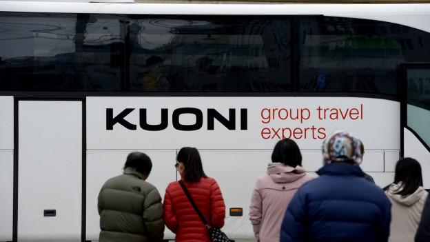 Asiatische Touristen stehen vor einem Kuoni-Touristenbus.