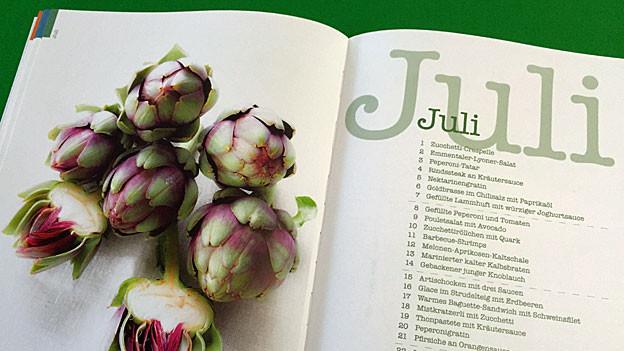 Eine Doppelseite aus einem Wildeisen-Kochbuch. Links sind Artischocken abgebildet, rechts steht «Juli», darunter ein Inhaltsverzeichnis.