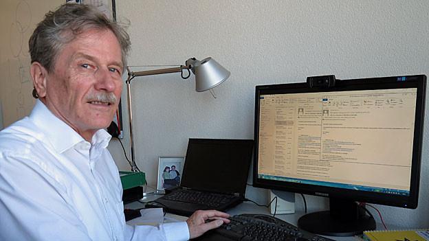 Der silberhaarige Bernhard Plattner sitzt in seinem Büro am Computer.